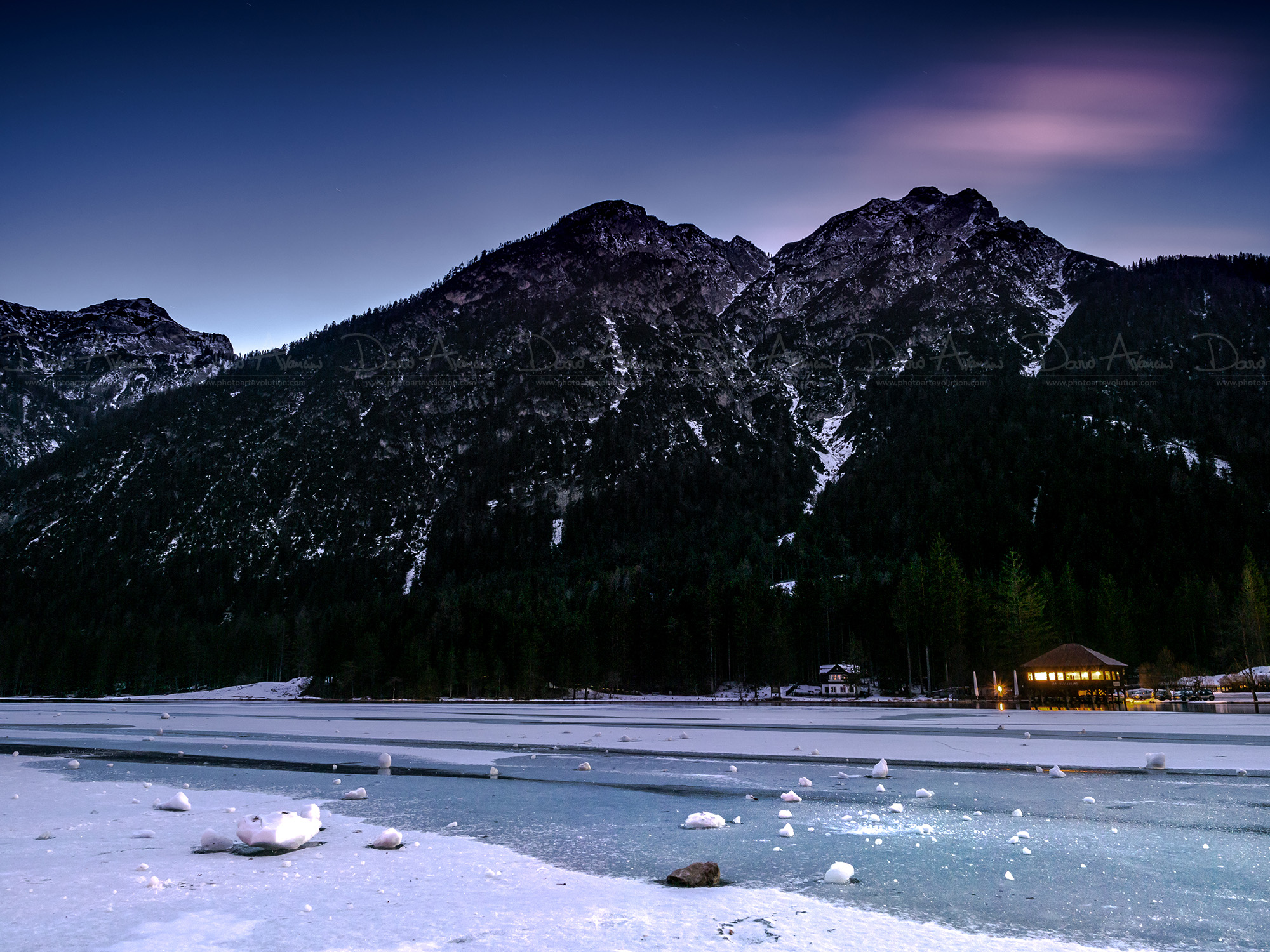 Sunset on the icy lake of Dobbiaco